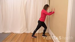 A woman is standing next to a wall, with her hands pressed against the wall. Her left leg is slightly bent with her toes almost touching the wall and her right leg parallel behind her to stretch her calf.