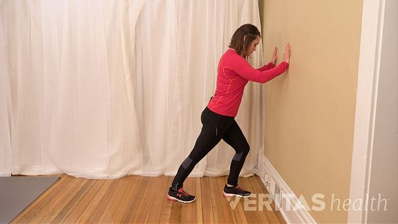 Woman performing the standing calf muscle stretch
