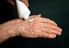 image of a hand with cream being applied from a tube
