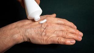 Applying topical pain reliever to right hand