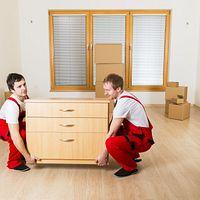 Two men team lifting a dresser.