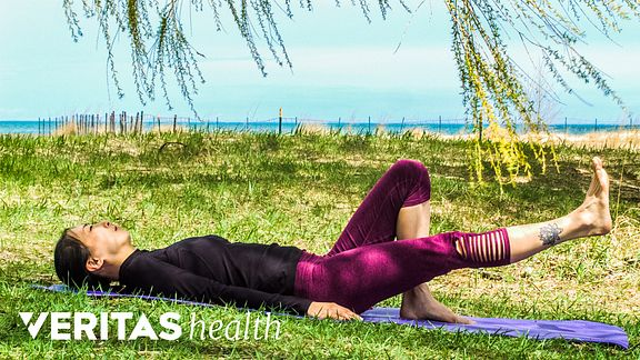 Woman lying on her back outdoors doing a supine leg raise