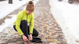 Woman tying her shoe outside on a winter run.