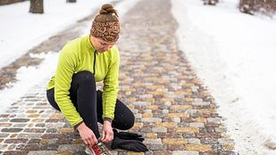 Woman tying her shoe outside on a winter run.