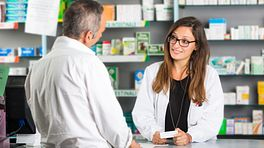 Customer and pharmacist discussing a medication
