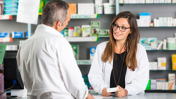 Man talking to a pharmacist about a prescription