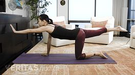 Woman performing the bird dog pose exercise