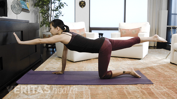 Image of woman performing the bird dog pose exercise for sacroiliac joint pain