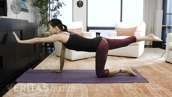 Woman doing opposite arm leg raise exercise for upper and middle back pain