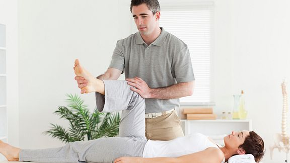 Physical therapist helping a patient perform a hip exercise