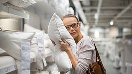 Woman squeezing a pillow in a store
