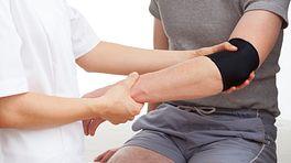 Doctor bracing a patient's elbow