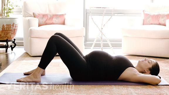 Pregnant woman lying on exercise mat in preparation for the pelvic tilt exercise