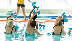 Group doing water aerobics in a pool with an instructor