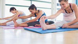 Yoga class participants doing a forward bend.