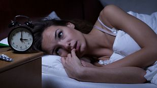 Woman awake with insomnia in her bed.