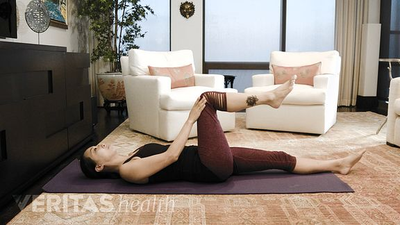 Woman doing the single knee to chest sacroiliac (SI) joint stretch