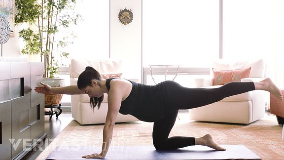 Pregnant women doing arm leg raise exercise