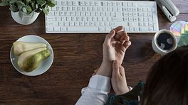 Woman's hands at a keyboard, one massaging the other