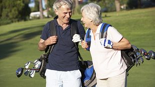 Couple walking happily on the golf course.