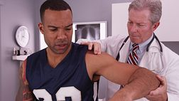 Man having his shoulder examined by a physician