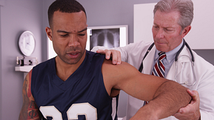 Image of a physician performing a shoulder exam on a male patient