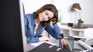 image of tired business woman sitting at her desk.