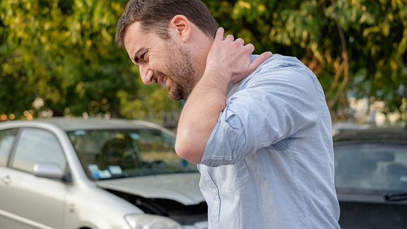 Image of man holding his neck and his damaged car in the background