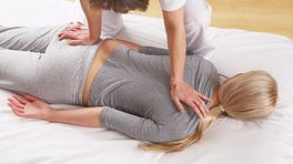 Client lying prone receiving a massage.