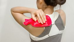 Woman applying a hot pack to her upper back