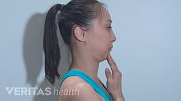 Profile view of a woman doing a chin tuck.