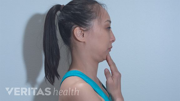 Side profile of woman performing the chin tuck exercise