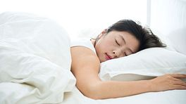 Woman sleeping on her stomach in a bed
