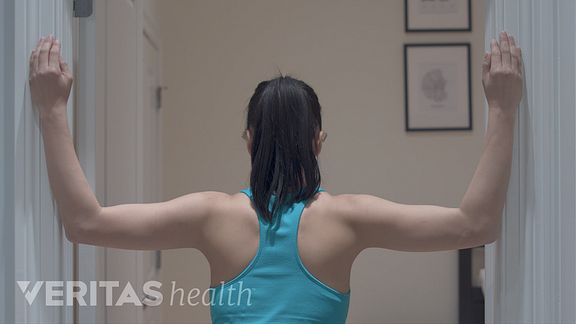 Woman doing the corner stretch exercise for upper and middle back pain