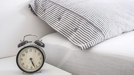 Alarm clock sitting next to a fresh bed and pillow.