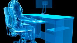 X-ray of person sitting at desk with proper posture