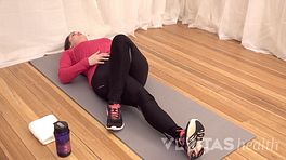 Woman lying on her back doing a piriformis muscle stretch.