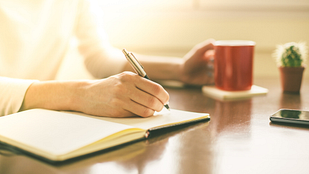 Photo a woman writing in a journal with a mug