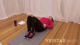 Woman lying supine doing Lumbar Rotation SI Joint Stretch