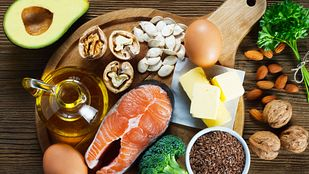 Spread of healthy foods including broccoli, salmon, eggs, olive oil, chia seeds, and avocado