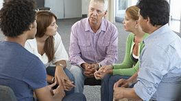Group of people of mixed ages sitting together and talking in a circle