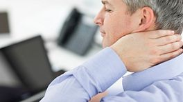 Man sitting at his computer grabbing neck in pain