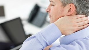 Man grabbing neck in pain