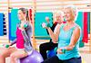 在运动类前辈和导师做健身球的图像的手的重量练习