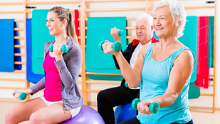 Image of seniors and instructor in an exercise class doing exercise ball exercises with hand weights