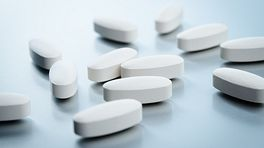 White, non-descript pills scattered on a table