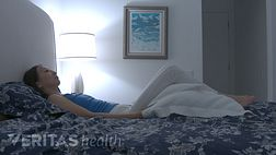 Woman laying on her back on the bed with a pillow under her knees.