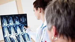 Doctor examining scans of a patient's spine.