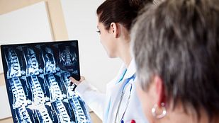 physician examining a cervical spine xray