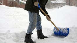 Lower body of a person shoveling snow